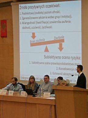 zdjęcie zkonferencji, paneliści usadzeni przy stole, wtle prezentacja jednego znich